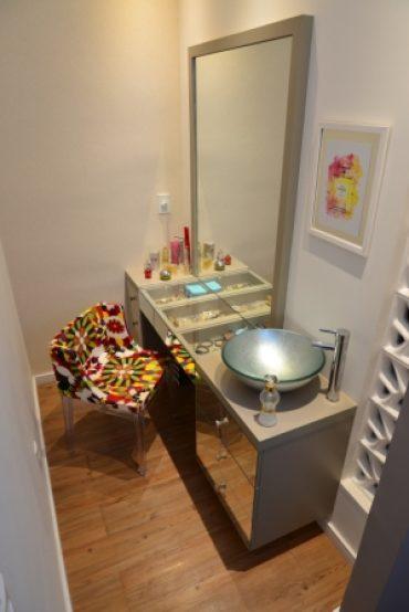 Area de maquiagem com espelho iluminado e bancada com divisão para jóias e maquiagem.